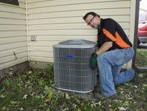 在空调器单位格栅之外的安装工清洁 图库摄影