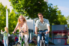 在空闲时间的都市夫妇骑马自行车在城市 图库摄影