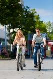 在空闲时间的都市夫妇骑马自行车在城市 免版税图库摄影