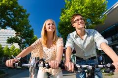 在空闲时间的都市夫妇骑马自行车在城市 免版税库存图片