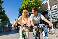 在空闲时间的都市夫妇骑马自行车在城市 库存照片