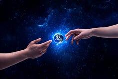 在空间感人的行星地球的手 免版税库存图片