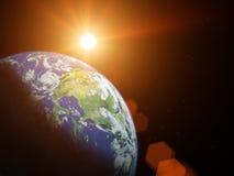 在空间的行星地球与太阳发光。 免版税库存图片
