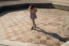 在穿着一条五颜六色的裙子的一个空的喷泉的愉快的年轻女人跳舞 免版税图库摄影