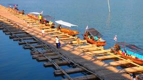 在穿过河的竹桥梁旁边的小船 库存图片