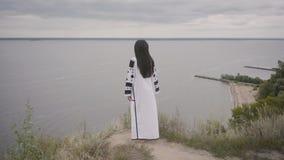 在穿长的夏天时尚礼服的可爱的非裔美国人的妇女的背面图走在背景的领域  影视素材