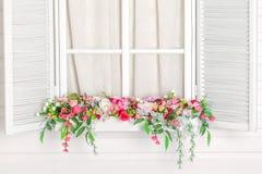在窗口下的开花的花床 与花的窗台 免版税图库摄影