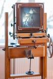 在窗口前面的一台古老葡萄酒木照相机,在屏幕上您能看到自然的投射 库存照片
