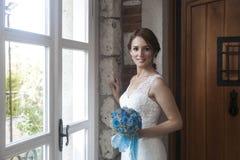 在窗口前面的愉快的新娘 库存照片