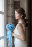 在窗口前面的愉快的新娘 免版税库存照片