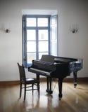 在窗口前面的钢琴 库存照片