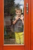 在窗口后的小男孩在雨中 库存图片