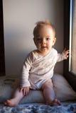 在窗口和微笑里坐一个小男孩的画象 情感概念 库存照片