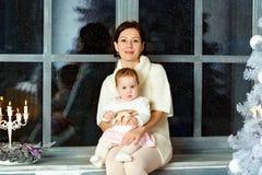 在窗口和拥抱的妈妈深色的开会小的逗人喜爱的胖的g 图库摄影