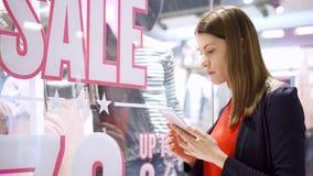 在窗口商店附近的少妇 桃红色销售额黄色 由智能手机的读书QR代码,检查在网上定价 股票录像