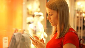 在窗口商店附近的美丽的可爱的少妇在购物中心 检查在她的智能手机的商店价格 影视素材
