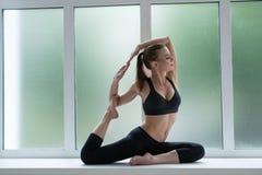 在窗口基石的俏丽的模型在瑜伽姿势 免版税库存照片