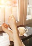 在窗口基石的妇女脚 概念放松 免版税库存照片