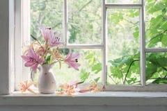 在窗口基石的百合花束在一个晴天 免版税库存照片