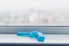 在窗口基石的蓝色玩具枪 免版税库存照片