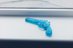 在窗口基石的蓝色玩具枪 免版税图库摄影