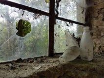 在窗口壁架的老牛奶瓶 库存图片