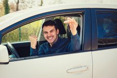 在窗口外面的偶然人司机陈列汽车钥匙 成功的年轻人买了一辆新的汽车,握紧庆祝的拳头 库存图片