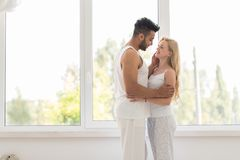 在窗口容忍、愉快的微笑西班牙男人和妇女附近的年轻美好的夫妇立场 免版税图库摄影