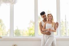 在窗口容忍、愉快的微笑西班牙男人和妇女附近的年轻美好的夫妇立场 库存图片