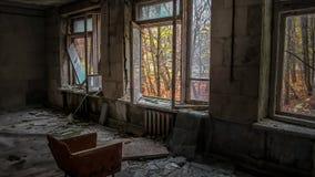 在窗口对面的椅子在一个老被破坏的被放弃的房子的屋子里在Pripyat在乌克兰 免版税库存照片