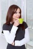 在窗口微笑附近的妇女饮用的咖啡 免版税库存图片
