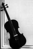 在窗口的中提琴 免版税库存照片