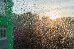 在窗口的大雨珠,都市日落背景 免版税库存照片