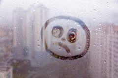 在窗口的有雾的玻璃与拉长的哀伤的面孔概念照片 库存照片