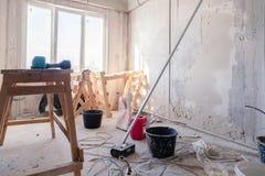 在窗口的木脚手架立场在一间大空的屋子,修理,涂灰泥,绘的墙壁,大厦工具,垃圾 ?? 库存图片