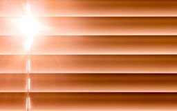 在窗口的橙色水平的窗帘通过t创造节奏 免版税库存照片