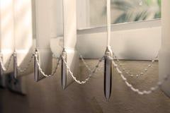 在窗口的现代垂直的织品窗帘 免版税库存照片