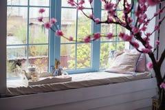 在窗口的盘子用茶和枕头 免版税库存图片