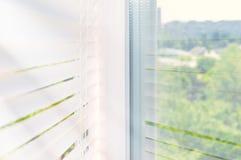 在窗口的闭合的塑料窗帘与在玻璃的反射 免版税库存照片