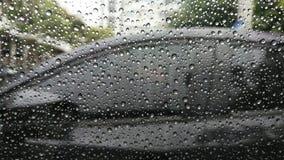 在窗口的雨下落与汽车 免版税库存图片