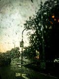 在窗口的雨下落在汽车的城市里面 库存图片