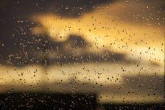 在窗口的雨珠在日落时间 背景波罗的海日落 库存图片