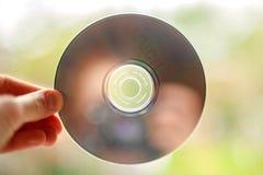 在窗口背景的音乐CD的女性手 免版税库存照片
