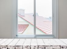 在窗口视图的木台式与屋顶房子 库存照片