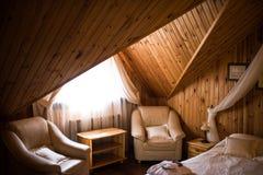 在窗口附近的两把扶手椅子在旅馆客房由木头制成 一间木屋子的内部 库存照片