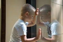 在窗口附近的哀伤的孩子 库存图片