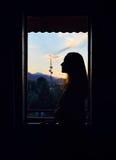 在窗口附近的妇女剪影 库存照片