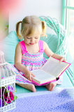 在窗口附近的小的逗人喜爱的女孩阅读书 免版税图库摄影