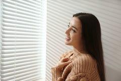 在窗口附近的年轻女人与软百叶帘 库存图片