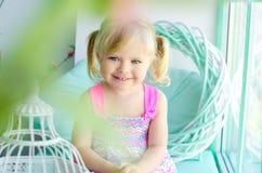 在窗口附近的微笑的小逗人喜爱的女孩 免版税库存照片